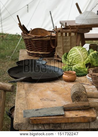 Black Pans, Salad And Knife On Wooden Table