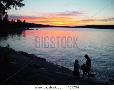 Silhouette Of Father And Son Fishing Against A Sunset At A Lake
