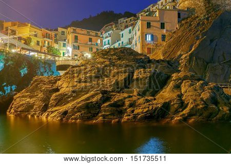 A view of the colorful traditional houses on the rock on sunset. The coast of Liguria. Manarola, Cinque Terre.