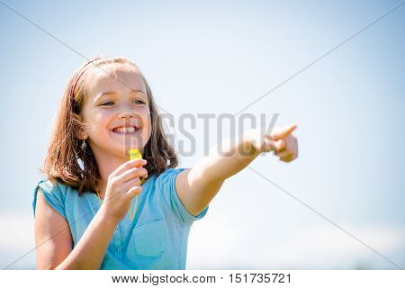 Smiling child blowing in whistle and pointing with hand - outdoor in nature