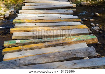 old wooden bridge of planks over the river