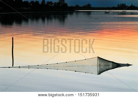 A geometrical fish trap reflected at sunset. . . blurred background