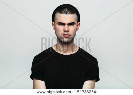 Studio portrait of aggressive angry young man looking at camera on gray background.