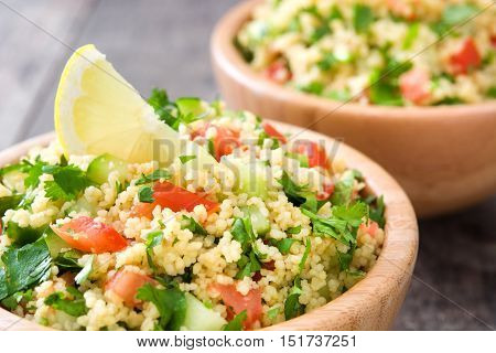 Tabbouleh salad with couscous on rustic wooden table