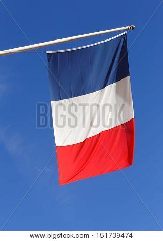 Frensh flag  hanging against a blue sky.