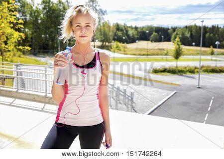 Portrait of young woman in sportswear holding water bottle on stairway