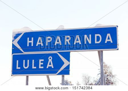Signpost with snow leads the way to the Swedish cities of Lulea and Haparanda