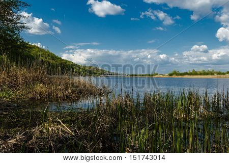 beautiful Blue Lake with yellow grass in the foreground and a blue sky with clouds