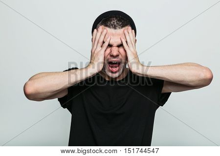 Really annoyed man in black t-shirt against grey background