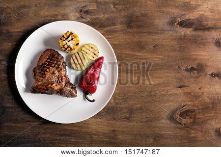 Grilled steak on brown wooden board with vegetables and spices, rustic background, top view