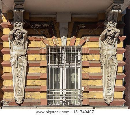 Window of old building with lattice and caryatids Odessa Ukraine
