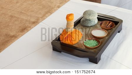Spa and wellness massage setting Still life with essential oil, salt and compress balls Outdoor summer background