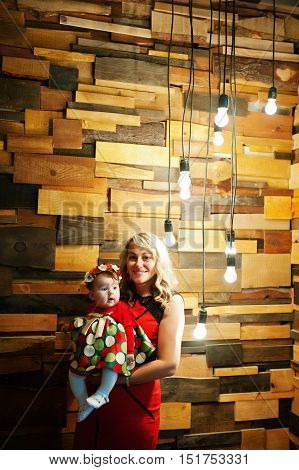 Mother Hold Her Baby Girl On Hand Background Wooden Wall With Enabled Light Bulbs