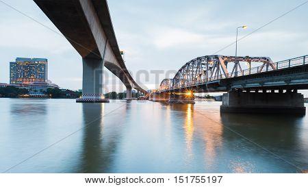 Under the bridge cross Bangkok river after sunset, Thailand