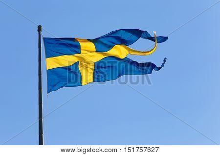 The Swedish three-tailed naval flag on blue sky.
