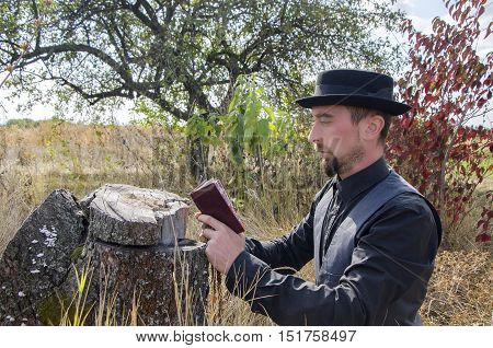 Young bearded priest prays in a garden