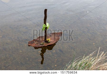 Closeup of a bark boat with mast floating on water.
