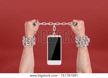 Human hands chained to the phone. Dependence on information technology. Technology addicted.