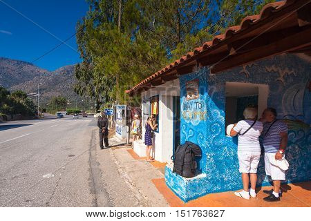 Bali Island Crete Greece - June 23 2016: People buying tickets on the bus and tourists waiting the bus on the bus stop near village Bali to destination Rethymno (Chania)