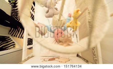 Baby lying in his cot and playing with Crib Mobiles. top view