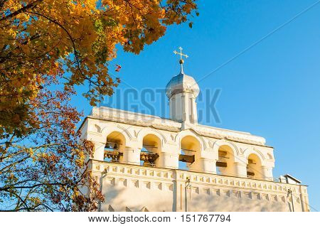 Architecture landscape-belfry of Saint Sophia Cathedral in Veliky Novgorod Russia. Architecture landmark framed by autumn trees against blue sky