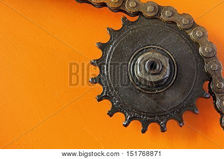 Metal cogwheel and chain taken closeup on orange background.