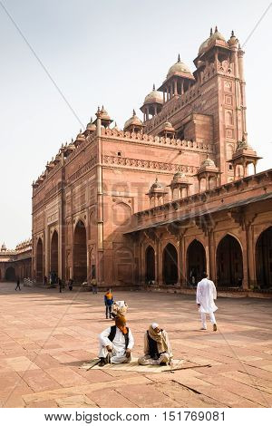 Fatehpur Sikri India - 2015 January 9 : The courtyard of the mosque Jama Masjid in Fatehpur Sikri with Indian worshippers sitting outside
