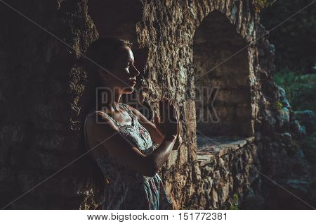 Young woman praying in Stari Bar old fortress, Montenegro. Girl silhouette in front of a sunset. Religion, Meditating, Spirituality concept.