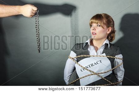 Upset businesswoman bound by contract terms and conditions. Helpless woman tied to chair become slave. Human hand holding chain. Business and law concept.