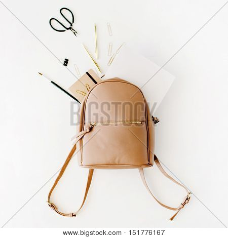 Brown leather backpack with female artist items on white background flat lay top view