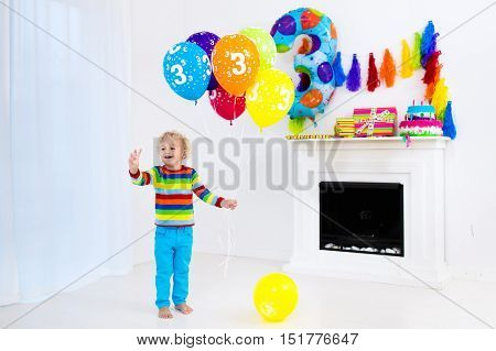 Child celebrating third birthday. Little boy opening presents and holding balloons in decorated room. Birthday party for kids.