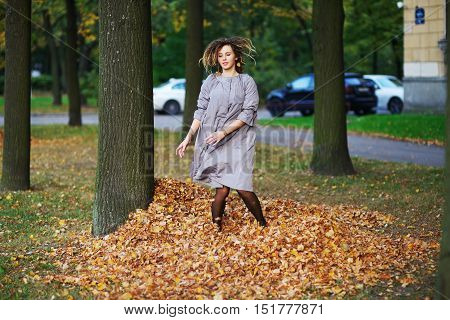 Beautiful smiling girl with dreadlocks in a lavender cloak having fun in the alley between the trees jumping on a pile of yellow leaves.