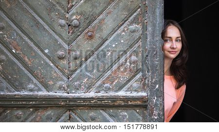 Young woman peeks out from behind big ancient doors.