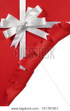 Christmas Or Birthday White Satin Gift Ribbon And Bow On Red Paper Background With Torn Open Corner