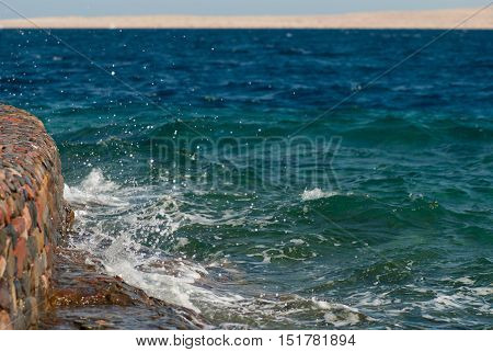 Photo of beautiful clear turquoise sea ocean water surface with ripples and bright splash on stone seascape background, horizontal picture.