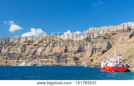 Red ship moored to pier. Santorini island view from the sea from boat in europe greece santorini island house and rocks the sky