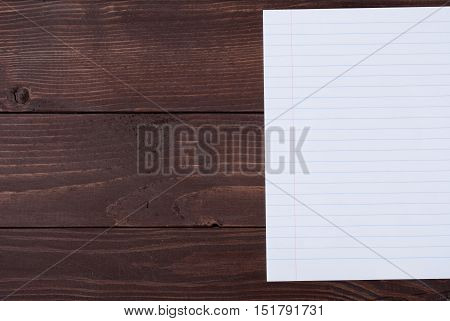 School stationery with copyspace on wooden board. Exercise-book on wooden table