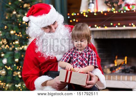 Santa Claus and kid boy holding gift box and sitting at fireplace