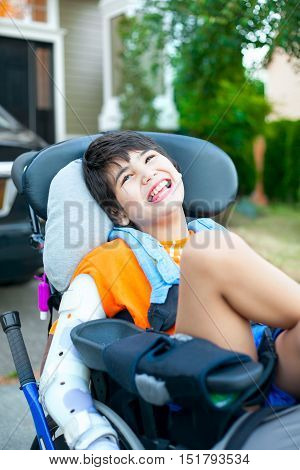Biracial ten year old boy sitting in wheelchair outdoors smiling and relaxing