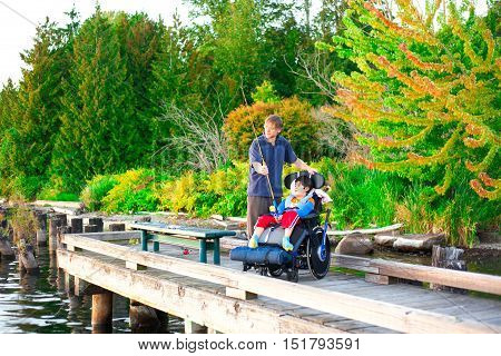 Caucasian father helping disabled ten year old son in wheelchair fish off pier