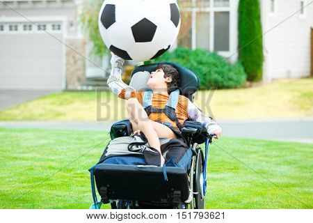 Ten year old biracial disabled boy in wheelchair playing with soccer ball at park