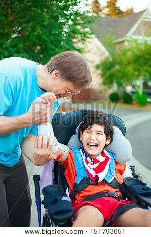 Caucasian father helping disabled ten year old son in wheelchair adjust orthotic arm guards outdoors. Child has cerebral palsy