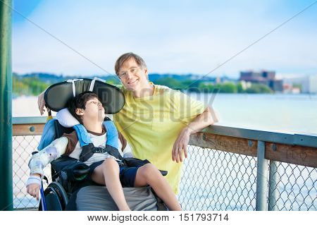 Caucasian father enjoying the lake with disabled ten year old son in wheelchair together