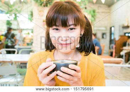 Portrait Of Asian Smile Women Holding Latte Art Coffee