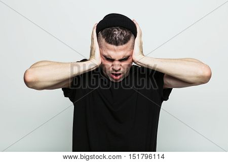 Man in black t-shirt against grey studio background that doesn't want to hear anything from you