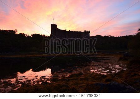 Beautiful sunrise over silhouetted Dunvegan castle at dawn