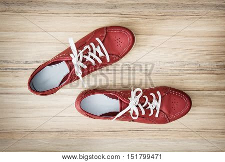 New red comfortable women's leather shoes on the wooden background. Beauty and fashion.