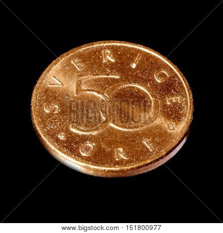 Swedish 50 ore denomination bronze coin in service 1992-2009 isolated on black background.