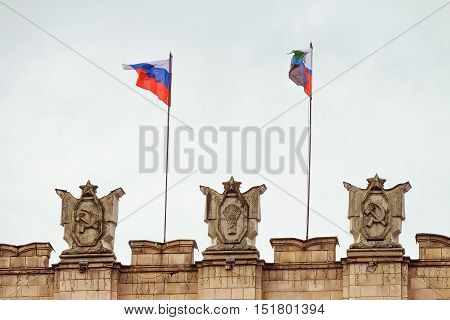 Fragment of parapet administrative government building with USSR symbols, flags of Russia and Belgorod region. Hammer and sickle, a sheaf. Typical pattern of Stalinist architecture.