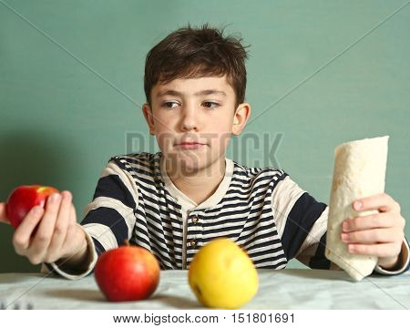 preteen handsome boy hold fast food roll and apples make choice